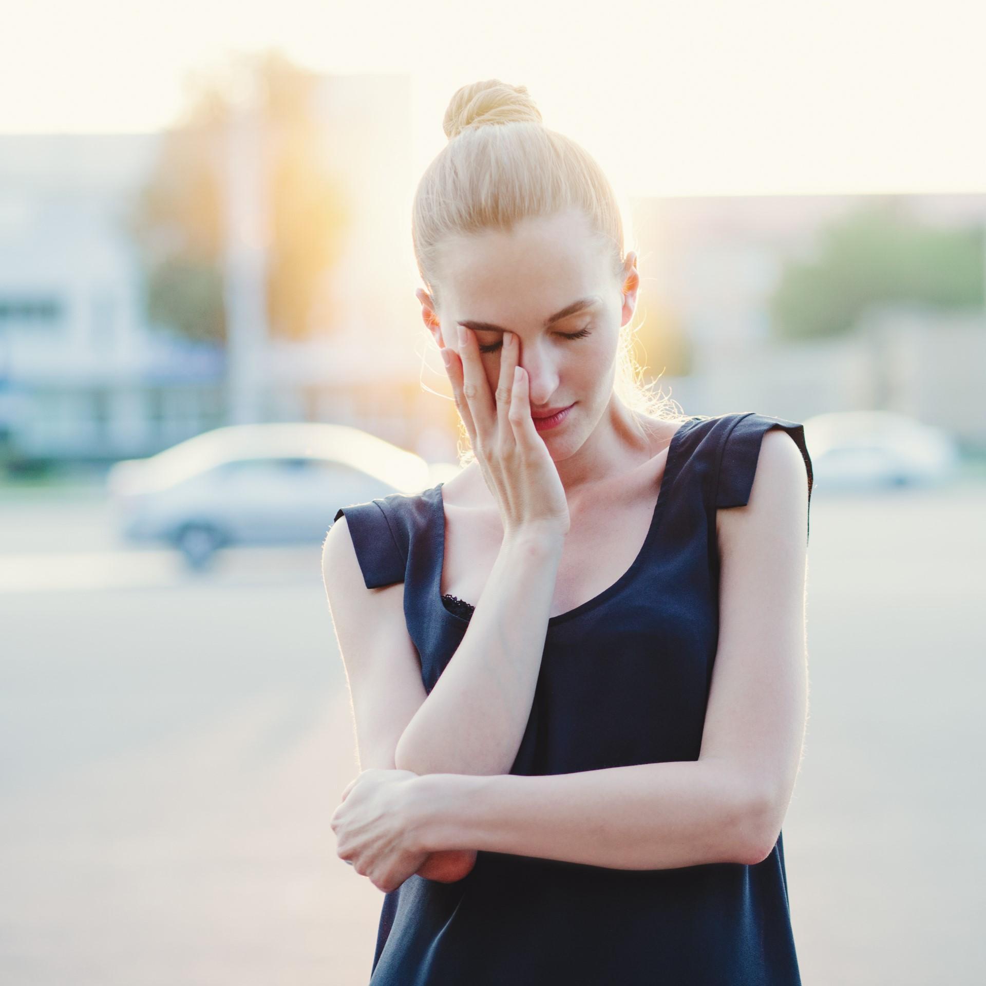 Emotive young beautiful woman posing on the street